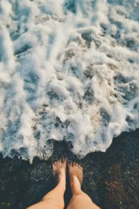 Feet near inland seashore.